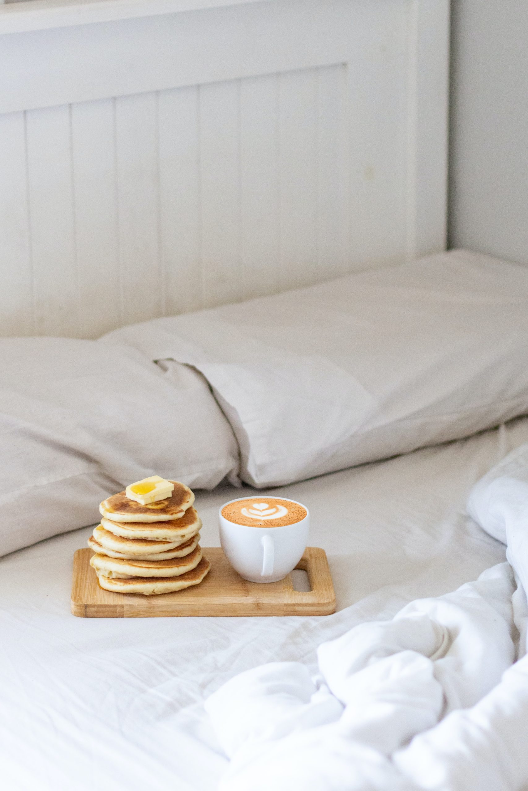 An image of an unmade bed, with pancakes and a latte, suggest self care ideas for Highly Sensitive People