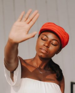 A woman wearing a red hat and holding her hand up to stop the physical symptoms of anxiety and depression.