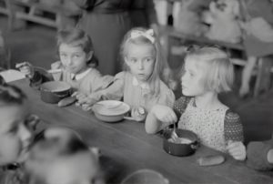 Three young girls at a table eating and are at risk for eating disorders.