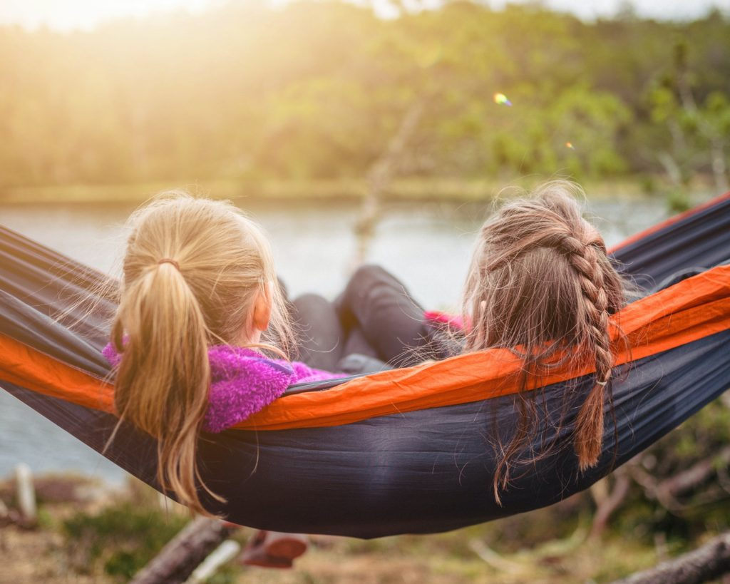Two tween girls are on a hammock enjoying nature.