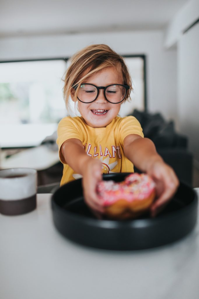 A child delighting in sitting at a table about to eat a delicious looking donut.