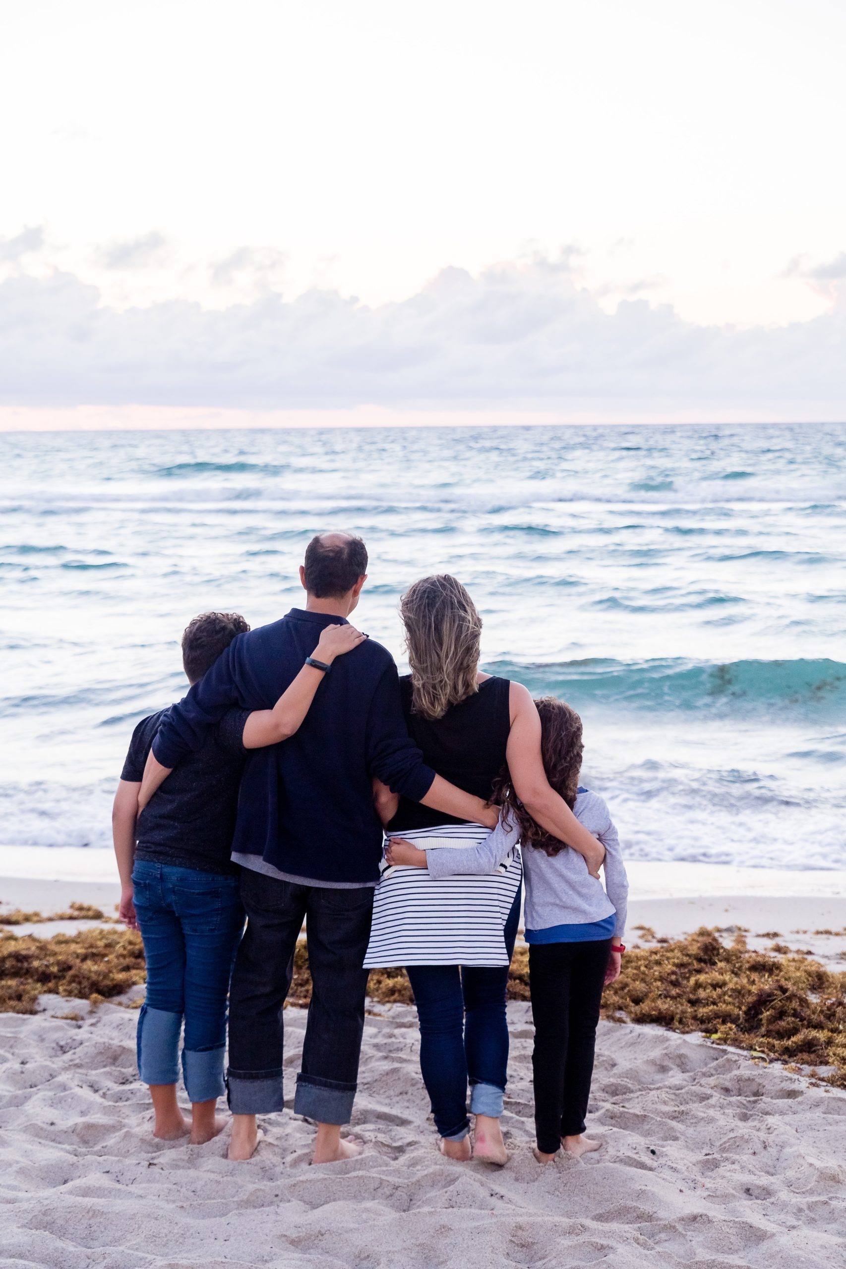 Two parents, their son and daughter on standing on a beach overlooking the ocean, representing the importance of recognizing early warning signs of eating disorders