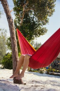 A woman's legs are dangling from a red hammock and is thinking about how to know if body image therapy is right for you