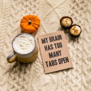 "A jpurnal titled ""My brain has too many tabs open"" is on a blanket along with a cup of coffee and snacks, ,symbolizing what it is like for a Highly Sensitive Person in an insensitive world."