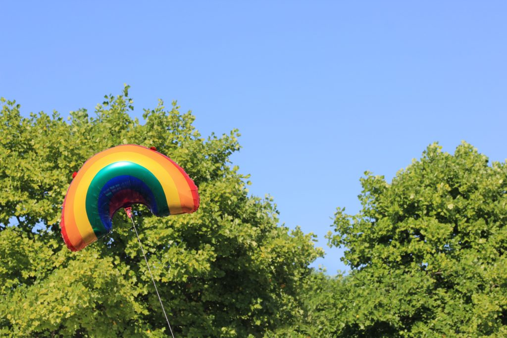 A large rainbow balloon in the treetop, against a blue sky, suggesting there is surprising and inspiring facts about anxiety and depression