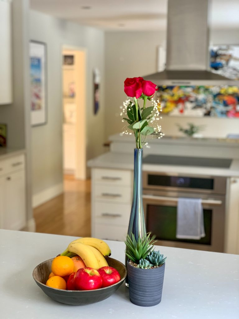 A neatly kept kitchen with a bowl of fruit and a vase with a flower on the counter suggest roommates have figured out how to live with a Highly Sensitive Person when you're sensitive too