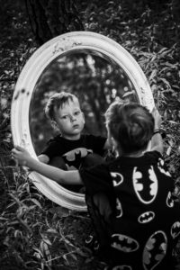 Boy looking in mirror at himself illustrating how hard it can be to tell if your son has body image issues