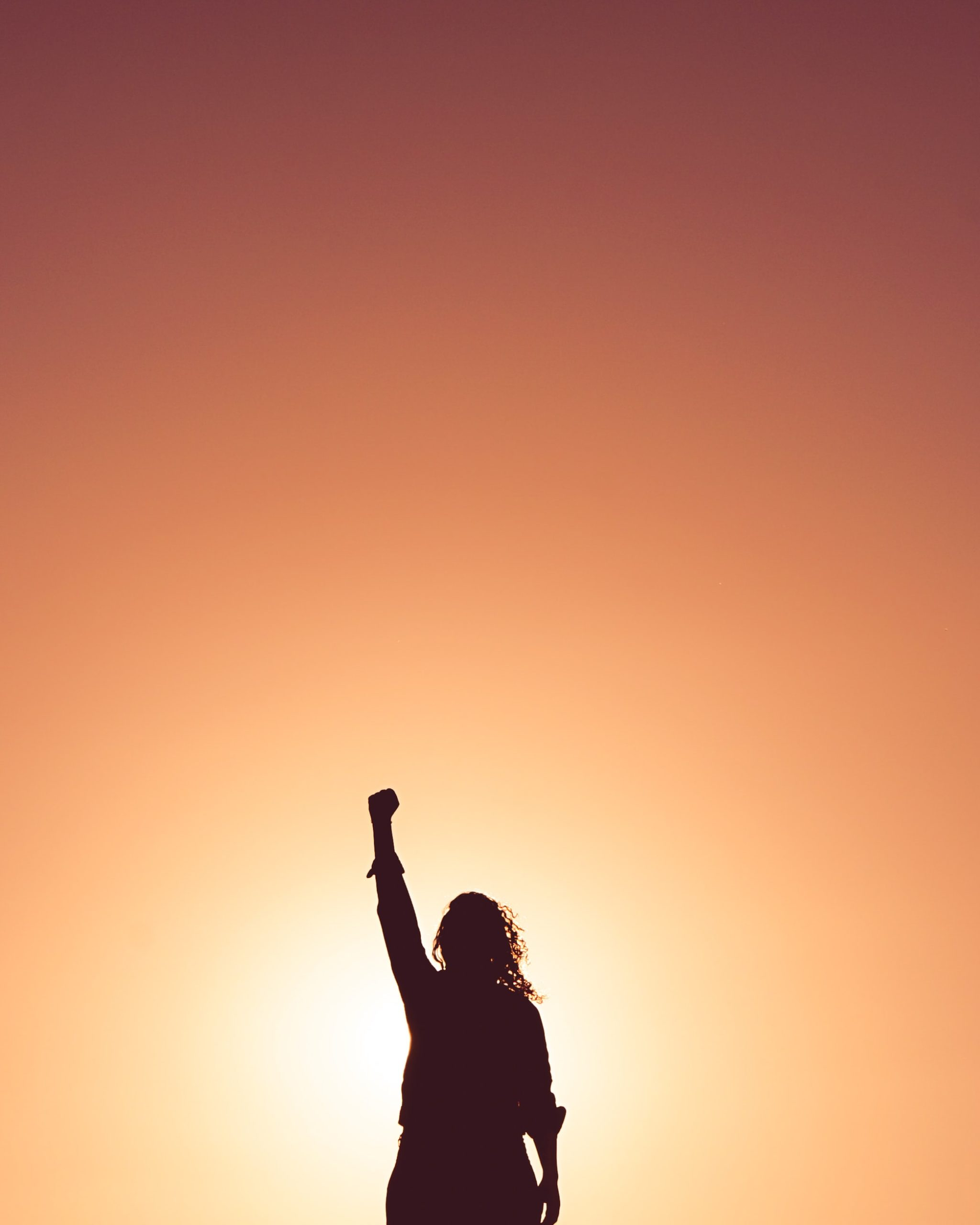 A sillhouette with her arm raised in victory after discovering the signs of anxiety and depression and starting therapy as a result.