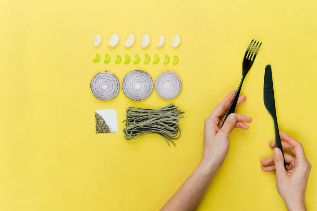 Four rows of food, witha woman's arm with fork in hand, demonstrating disordered eating.