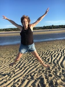 The image of a woman jumping for joy on a beach, representing a Highly Sensitive Person thriving