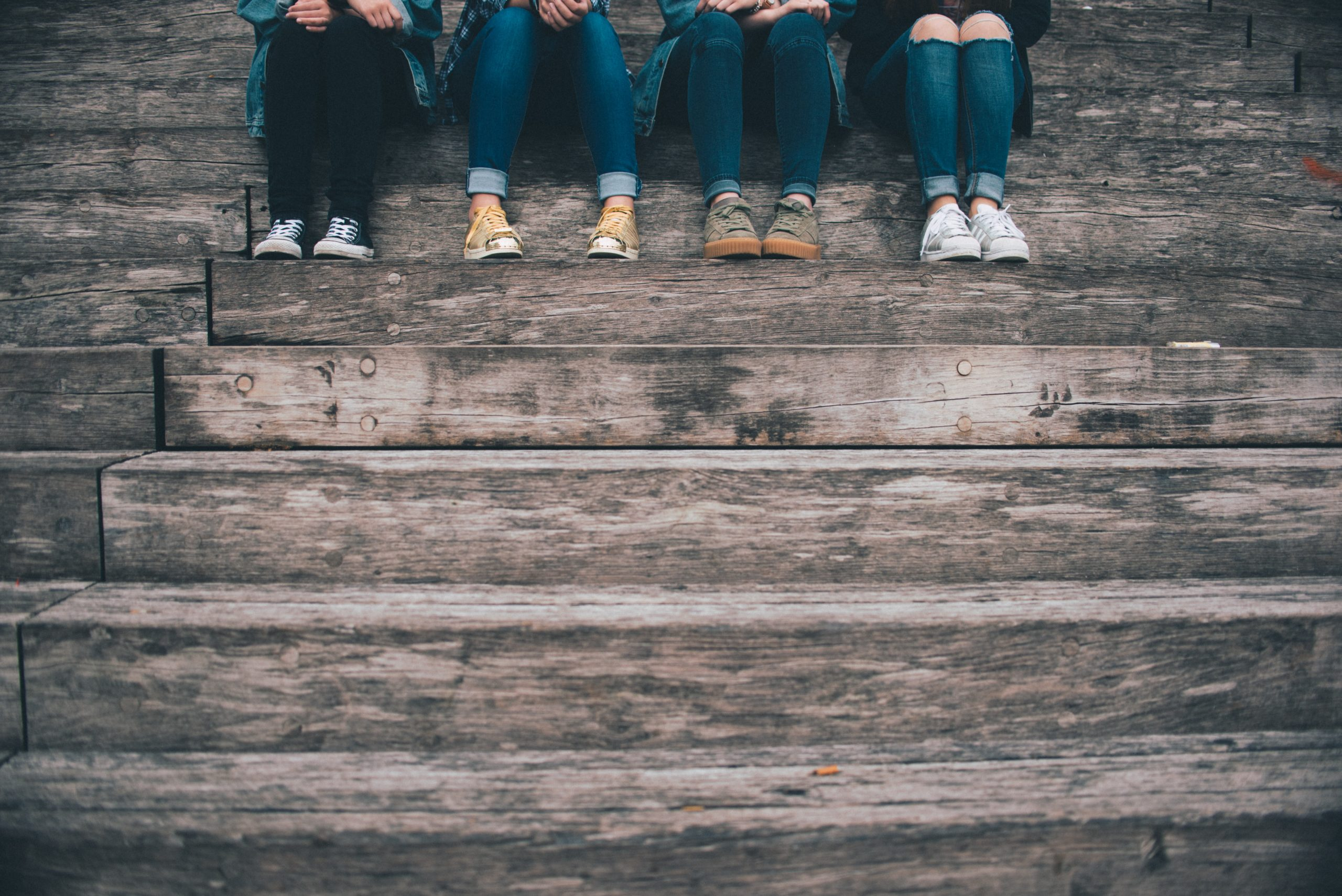 A photo of four girls of the tween years are sitting on a step, with just their legs showing from the knee down. They represent some of the influences on body image at that age.