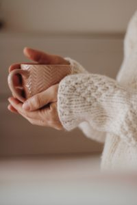 A woman's hands are holding a cup of tea, suggesting she is using the warmth of the cup as a way to manage anxiety as a Highly Sensitive Person.