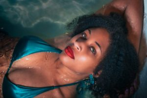 A photo from the chest up of an attractive woman with red lipstick and a bikini top laying n in water with a seductive expression.