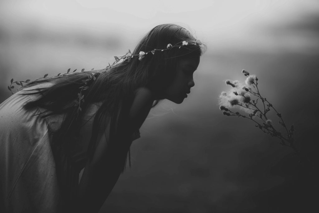black and white photo of an angelic girl bending over to smell a flower