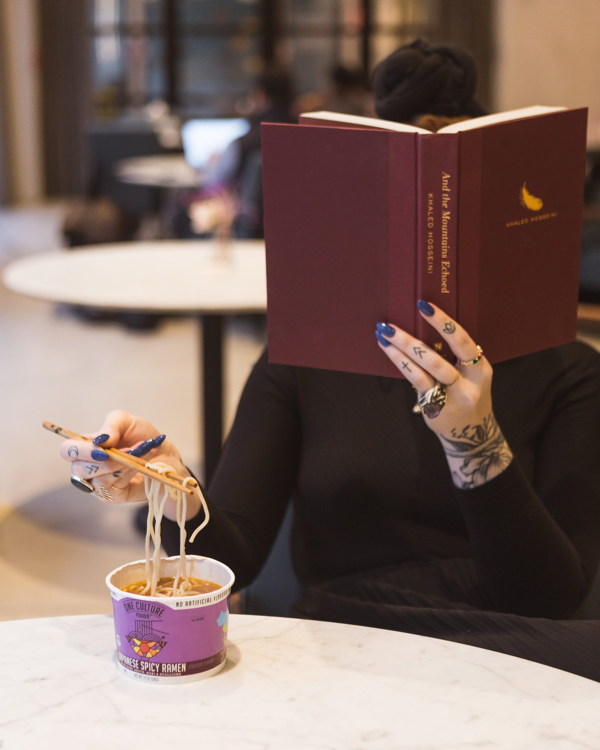 A photo of a woman seated at a table alone, eating soup, reading a book that she is holding in one hand and that is blocking her face.