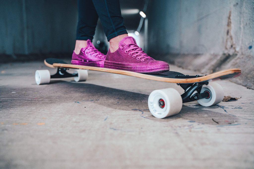 A woman's feet in purple sneakers on a skateboard.