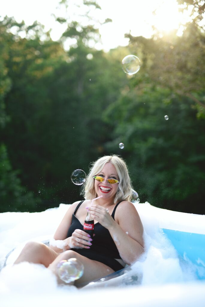 A joyous woman in a pool, seated in an inflatable and smiling