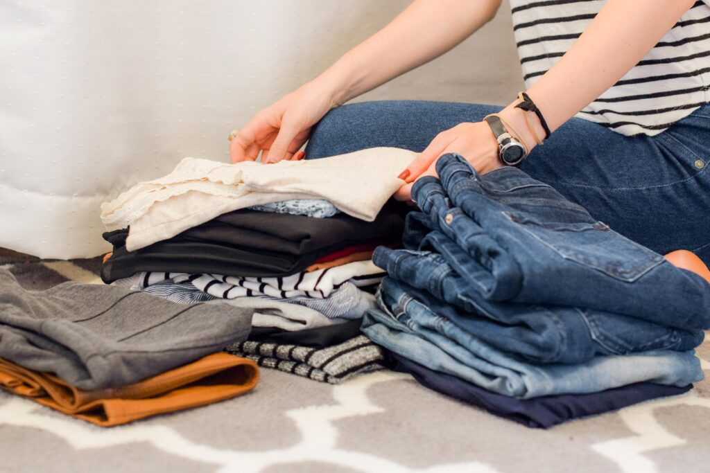 A photo of a woman folding clothes, with only her arms visible.