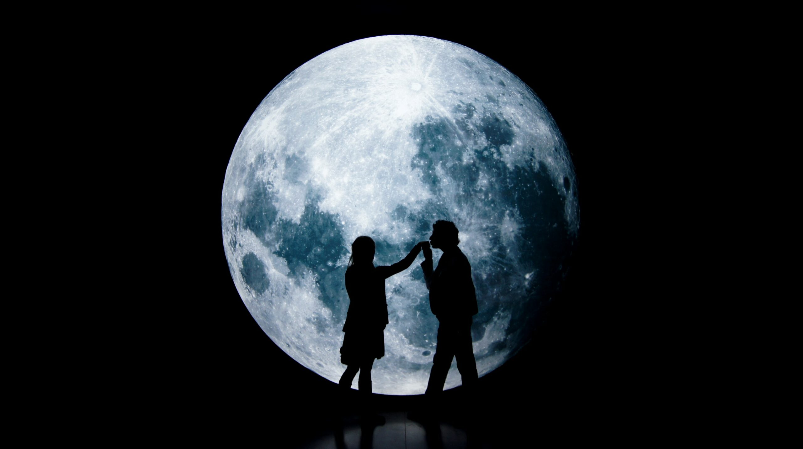 Sillhouette of a couple dancing together in the front of a large moon.