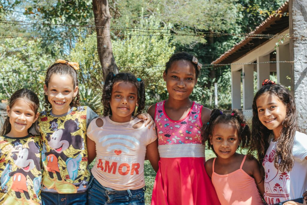 A group of 6 smiling girls, ranging in age from about 7-11, appearing not to have body image problems.