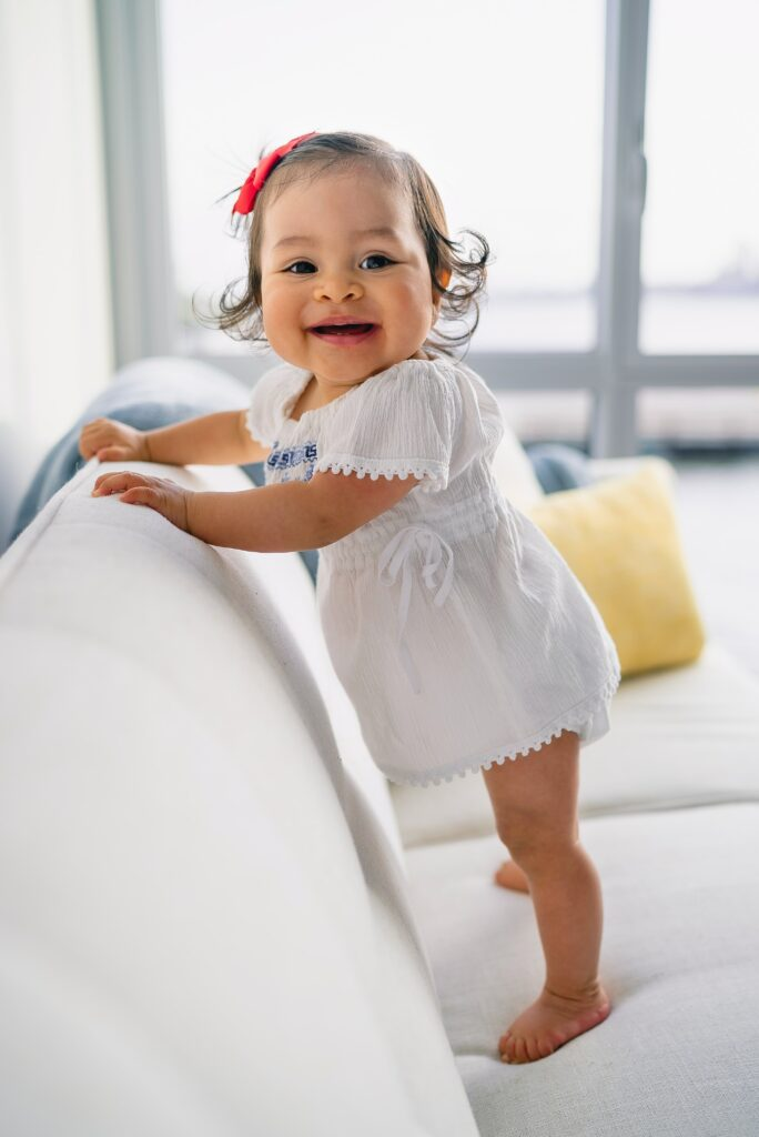 A toddler proudly standing on a couch, demonstrating no body image problems;