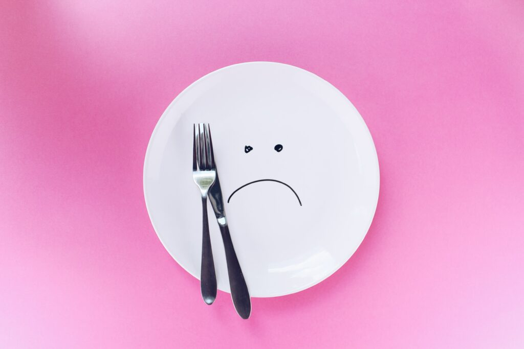 A picture of a white plate and a fork and knife on it. There is a frown face  drawn on the plate.