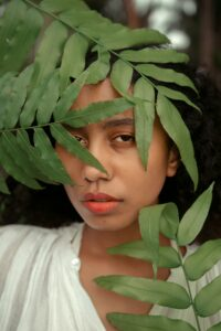 A woman peering through leaves of a branch appears depressed and anxious, as if looking to better understand what her diagnoses mean.