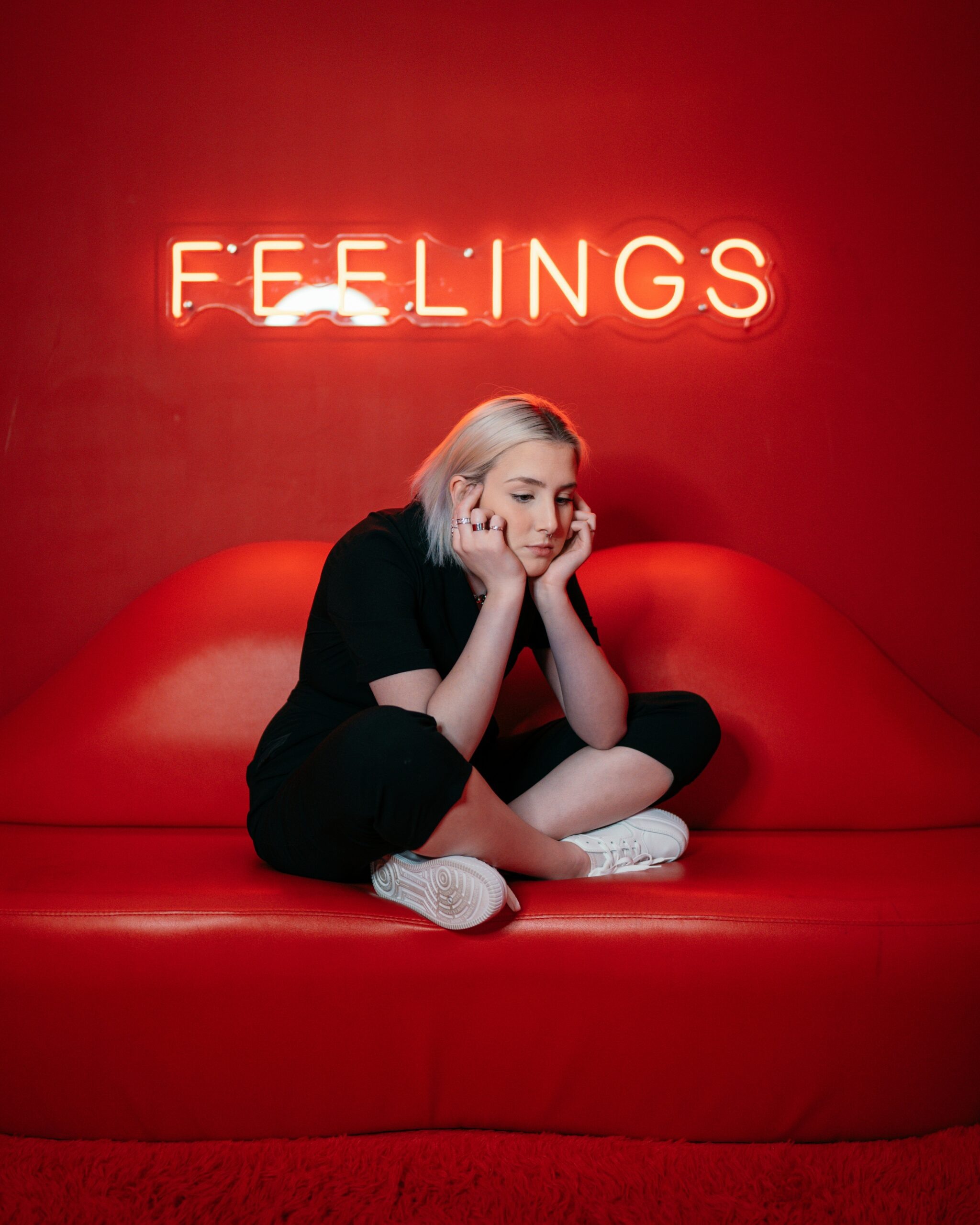 """A woman sitting on a red couch in front of a lit sign """"Feelings"""", appearing to be someone who could benefit from tips to manage depression and anxiety flareups"""
