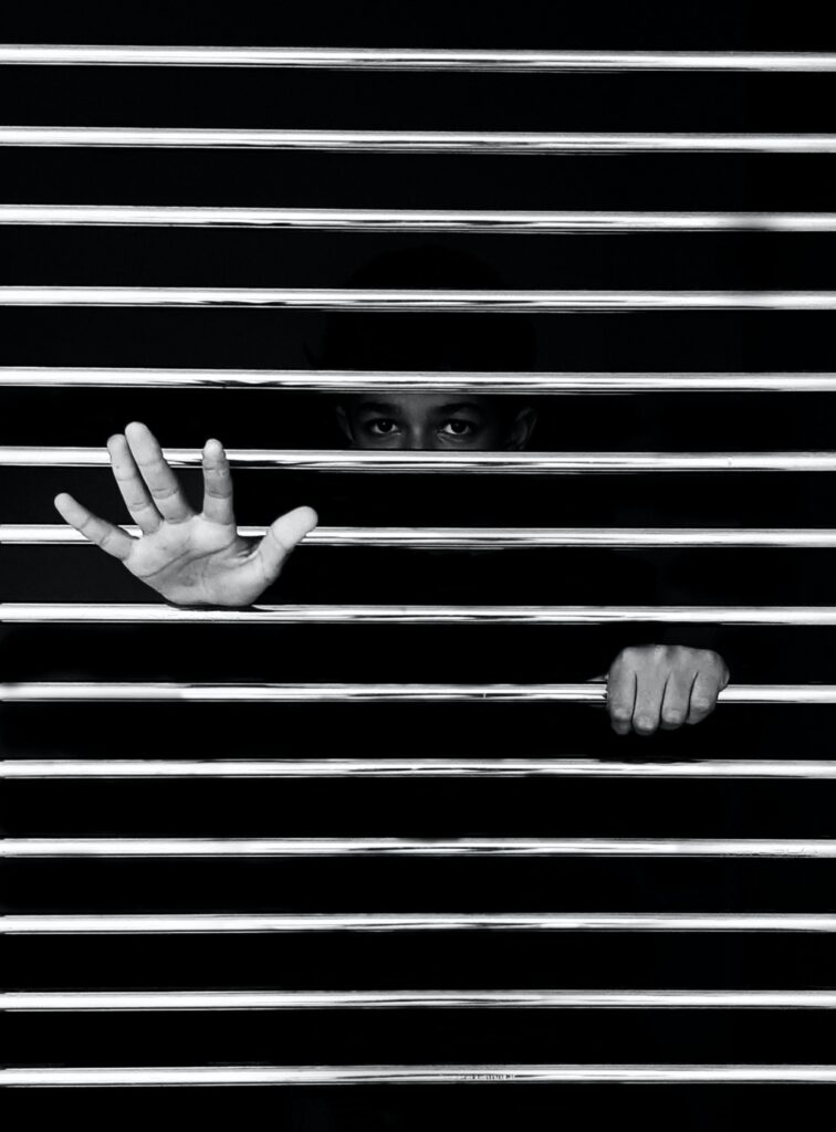 The hands of a woman through the horizontal slats of a blind, representing the stress of someone with depression and or eating disorders